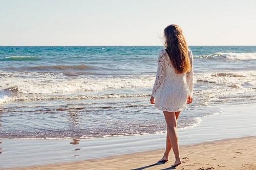 kobieta w bialej sukience na plaży